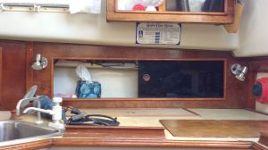 Lying on the galley counter on my back - with a boat cushion underneath. Inside the cabinet, underneath the liner.
